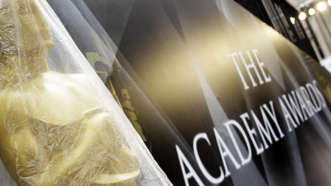 An Oscar statue is seen covered in plastic on the red carpet for the 83rd Academy Awards outside the Kodak Theatre in Los Angeles, Friday, Feb. 25, 2011. The Academy Awards will be held Sunday. (AP Photo/Matt Sayles)