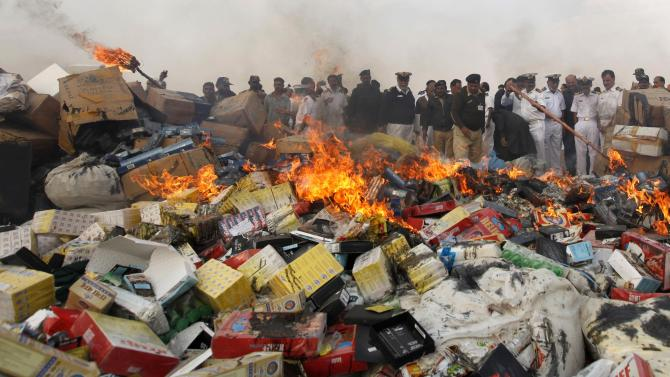 Customs officials gather to burn a pile of contraband and narcotics on the outskirts of Karachi