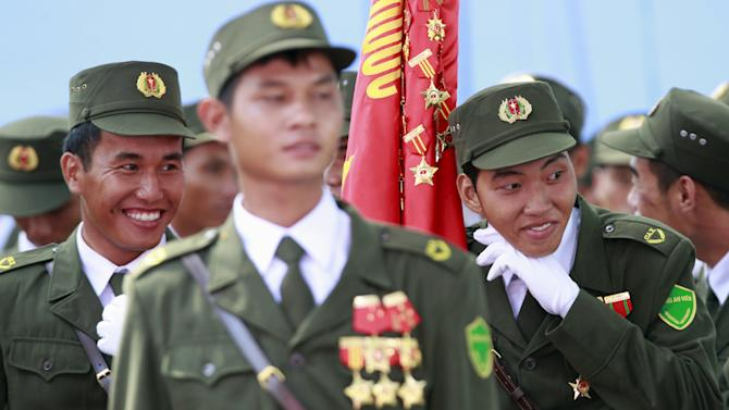 Vietnamese village policemen joke during a rehearsal for a military parade as part of the 40th anniversary of the fall of Saigon in southern Ho Chi Minh City (formerly Saigon City), Vietnam