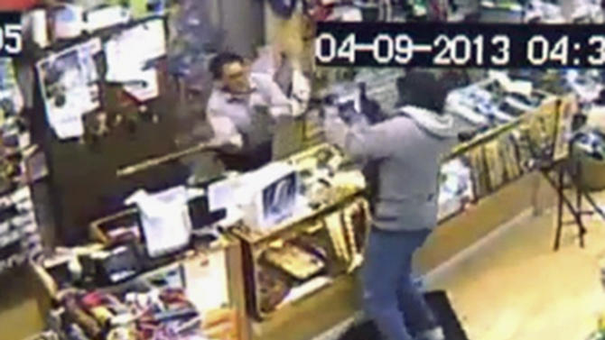 In this image taken from Tuesday, April 9, 2013 surveillance video provided courtesy of Quizhpe Gifts & Fashion, shop owner Luis Quizhpe, left, uses a baseball bat to fight off an armed robber at his shop in Chicago's Logan Square neighborhood. The gunman fired multiple shots at Quizhpe, hitting him in the leg. But the wound failed to stop the shop owner's vigorous counterassault with a baseball bat against the pair of robbers. One man was charged with attempted murder and armed robbery and officers are searching for a second suspect in the incident. (AP Photo/Courtesy Quizhpe Gifts & Fashion)