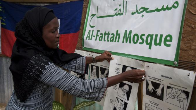 In this Sept. 28, 2012 photo, Darlene Derosier, 43, a Muslim, posts a how-to sign on the Islamic tradition of washing parts of the body in preparation for prayer at the Al-Fattah Mosque in Gressier, Haiti.  Islam has won a growing number of followers in this impoverished country, especially after the catastrophic earthquake in 2010 that killed hundreds of thousands and left millions more homeless. Derosier said she was drawn to the religion's preaching of self-discipline, emphasis on education and attention to cleanliness. The constant washing, she said, helps her and other Muslims avoid cholera, the waterborne illness that health officials say has sickened hundreds of thousands and killed thousands since surfacing after the quake. (AP Photo/Dieu Nalio Chery)