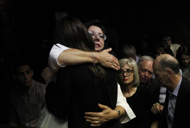Relatives of Oscar Pistorius hug each other ahead of court proceedings at the Pretoria magistrates court
