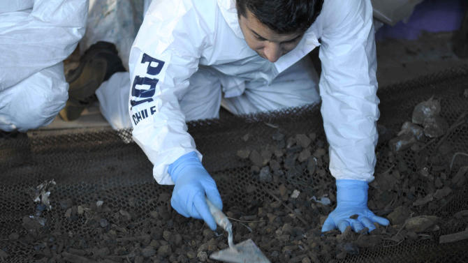 In this April 19, 2013 photo released by Chile's Police Investigative Unit on Thursday, April 25, 2013, an investigator collects samples of dirt at a farm used by a sect that is accused of burning a baby alive, in Colliguay, near the Chilean port of Valparaiso. Police on Thursday, arrested four people accused of burning a baby alive in a ritual because the leader of the sect believed that the end of the world was near and that the child was the antichrist. (AP Photo/ Chile's Police Investigative Unit)