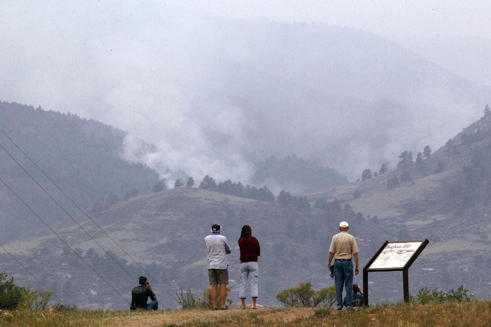 People watch from Bingham Hill as the High Park wildfire burns west of Fort Collins, Colo., on Tuesday, June 12, 2012. The fire which started on Saturday has burned more than 40,000 acres and one person is dead as firefighters struggle to contain the blaze. (AP Photo/Ed Andrieski)