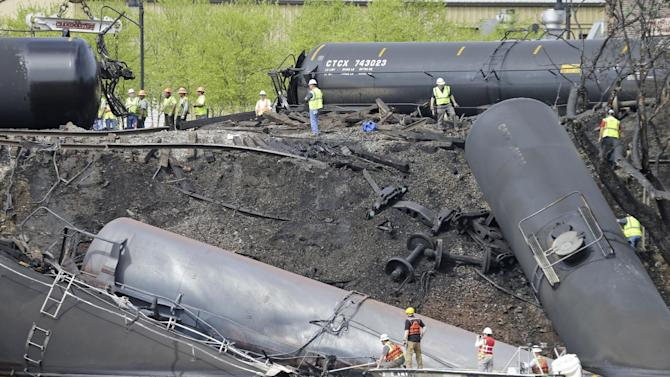 Survey crews in boats look over tanker cars as workers remove damaged tanker cars along the tracks where several CSX tanker cars carrying crude oil derailed and caught fire along the James River near downtown Lynchburg, Va., Thursday, May 1, 2014. Virginia state officials were still trying Thursday to determine the environmental impact of the train derailment. (AP Photo/Steve Helber)