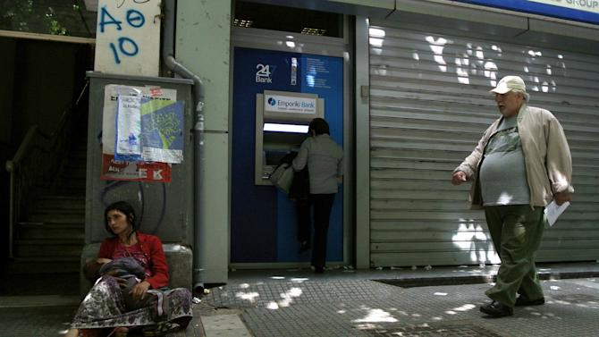 A woman receives money from an ATM machine outside Greece's Emporiki bank as a woman holds her child on the street at the northern port city of Thessaloniki, Greece, on Wednesday, May 23, 2012. Greece's four biggest commercial banks will receive an euro 18 billion ( $23 billion) cash infusion from the European bailout fund. (AP Photo/Nikolas Giakoumidis)