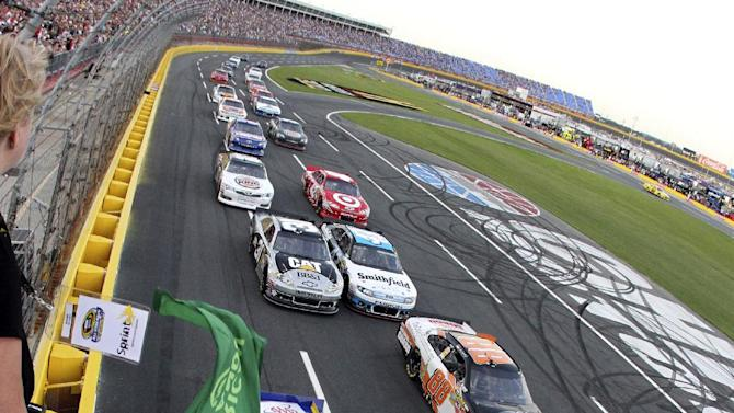 In this photo provided by HHP, Martin Truex Jr (56) and Dale Earnhardt Jr (88) lead the field at the start of the NASCAR Sprint Showdown auto race in Concord, N.C., Saturday, May 19, 2012. (AP Photo/HHP, Brian Lawdermilk)