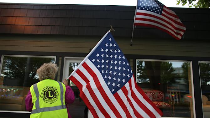 Susan Potemkin of the Lake City Lions Club prepares to hang a flag as a crew of Lions Club members place flags on businesses in north Seattle and Shoreline on Flag Day, Friday, June 14, 2013.  (AP Photo/seattlepi.com, Joshua Trujillo)