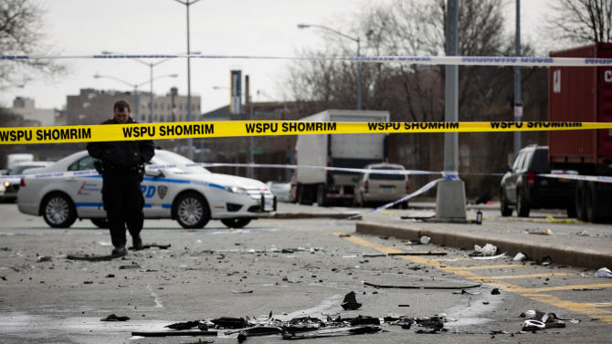 Debris from a fatal accident that claimed the lives of two expectant parents litter Kent Avenue, Sunday, March 3, 2013, in the Brooklyn borough of New York. A driver struck the car the couple were riding in early Sunday morning, killing both parents while their baby, who was born prematurely, survived and is in critical condition. (AP Photo/John Minchillo)