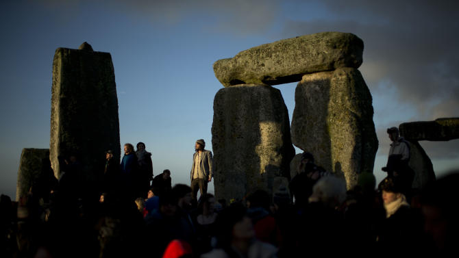 "People soak up the sun after its rise at the ancient stone circle of Stonehenge, in southern England, as access to the site is given to druids, New Age followers and members of the public on the annual Winter Solstice, Friday, Dec. 21, 2012.  Doomsday hour is here and so still are we.  According to legend, the ancient Mayans' long-count calendar ends at midnight Thursday, ushering in the end of the world. Didn't happen.  ""This is not the end of the world. This is the beginning of the new world,"" Star Johnsen-Moser, an American seer, said at a gathering of hundreds of spiritualists at a convention center in the Yucatan city of Merida, an hour and a half from the Mayan ruins at Chichen Itza. (AP Photo/Matt Dunham)"