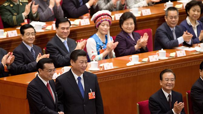 Newly-named Chinese Premier Li Keqiang, left, poses with Chinese President Xi Jinping as former Chinese Premier Wen Jiabao, right, and delegates applaud during a plenary session of the National People's Congress at the Great Hall of the People in Beijing Friday, March 15, 2013. China named the Communist Party's No. 2 leader, Li, premier on Friday as a long-orchestrated leadership transition nears its end, leaving the new leaders to confront uneven economic growth, unbridled corruption and a severely befouled environment that are stirring public discontent. (AP Photo/Andy Wong)