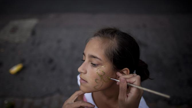 """Sol Basualdo, a member of the murga """"Los amantes de La Boca,"""" has her makeup done in preparation for carnival celebrations in Buenos Aires, Argentina, Saturday, Feb. 2, 2013. Argentina's carnival celebrations may not be as well-known as the ones in neighboring Uruguay and Brazil, but residents of the nation's capital are equally passionate about their """"murgas,"""" or traditional musical troupes. The murga """"Los amantes de La Boca,"""" or """"The Lovers of The Boca"""" is among the largest, with about 400 members. It's a reference to the hometown Boca Juniors, among the most popular soccer teams in Argentina and the world. (AP Photo/Natacha Pisarenko)"""