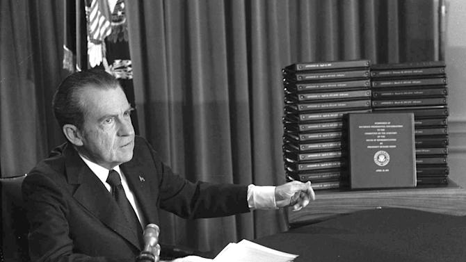 """FILE - In this April 29, 1974 file photo, President Richard M. Nixon points to the transcripts of the White House tapes in Washington, D.C., after he announced on television that he would turn over the transcripts to House impeachment investigators. During the Watergate hearings many Americans were shocked by Nixon's liberal use of profanities on the tapes, which made """"expletive deleted"""" a pop-culture catchphrase. (AP Photo/File)"""