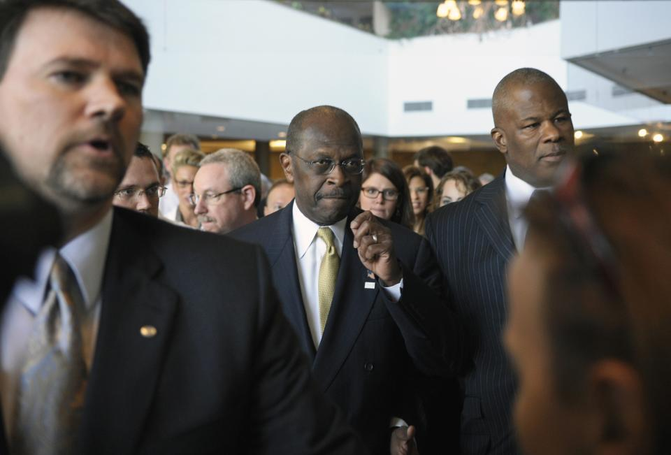 Republican presidential candidate Herman Cain, center, is surrounded by security and staff as he walks through a hotel lobby in Alexandria, Va., Wednesday, Nov. 2, 2011, before speaking after meeting with doctors attending the Docs4PatientCare conference. (AP Photo/Cliff Owen)