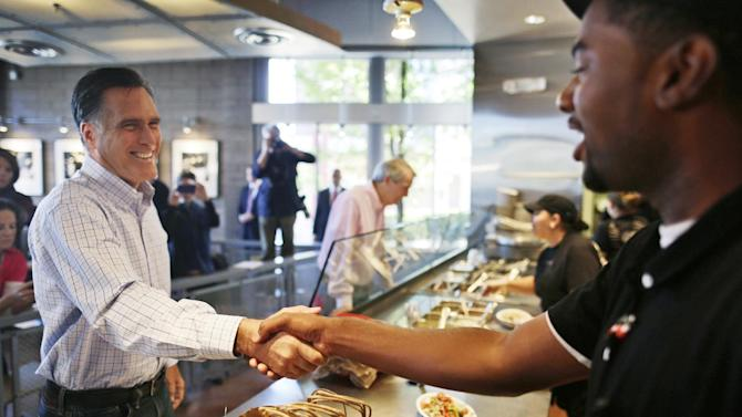 Republican presidential candidate, former Massachusetts Gov. Mitt Romney, accompanied by Sen. Rob Portman, R-Ohio, shakes hands with a worker as he makes an unscheduled stop at a Chipotle restaurant in Denver, Tuesday, Oct. 2, 2012. (AP Photo/Charles Dharapak)