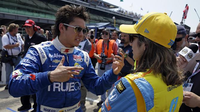 Sebastian Saavedra, of Colombia, left, talks with Ana Beatriz, of Brazil, after they both qualified on the second day of qualifications for the Indianapolis 500 auto race at the Indianapolis Motor Speedway in Indianapolis  Sunday, May 19, 2013. (AP Photo/Tom Strattman)