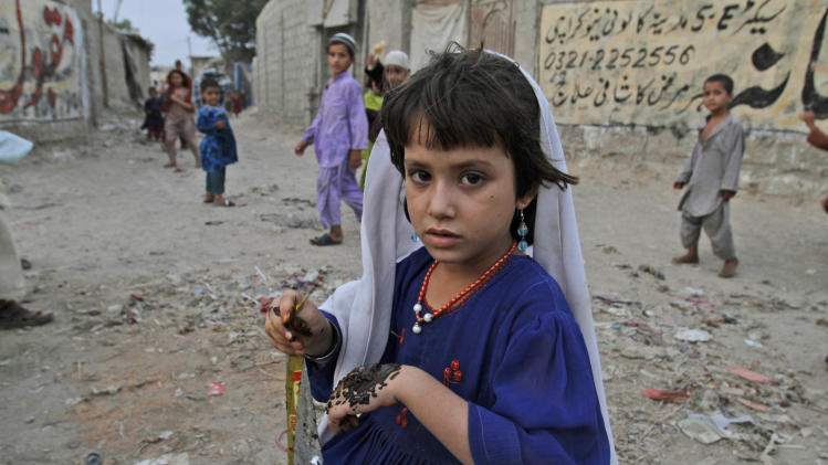 Afghan refugee girl, Fatima Gu, 7, looks on while putting henna on her hand, in a neighborhood on on the outskirts of Karachi, Pakistan, Monday, June 20, 2011. World Refugee Day is observed on Monday. (AP Photo/Shakil Adil)