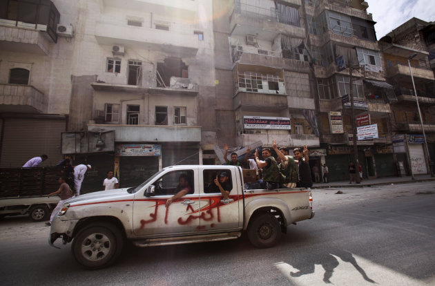 "In this Tuesday, Sept. 11, 2012 photo, Syrian rebel fighters flash the victory sign while moving past a building destroyed partly in a government shelling in Aleppo, Syria. Arabic reads on the vehicle, ""Free army"". Rebels have taken a major stride in uniting their ranks in the battle for Syria's largest city, giving them hope they could tip the balance in three-months of bloody stalemate in Aleppo, one of the biggest prizes of the civil war. The question is how much more destruction the city can bear. Regime troops are retaliating with heavier bombardment, and civilians are bearing the brunt, their neighborhoods left in rubble. (AP Photo/Muhammed Muheisen)"