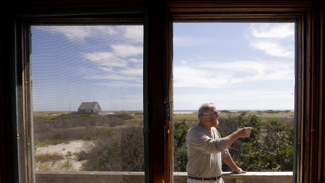 In this Aug. 23, 2011 photo, Roger Carroll, an occupant in one of the 11 cottages on North Beach Island in Chatham, Mass., stands on the deck outside his cottage. Five of the 11 dwellings, which are owned by the federal government and leased, are slated to be torn down and must be vacated by mid-September. The Carrolls lease one of the cottages scheduled for demolition. (AP Photo/Stephan Savoia)