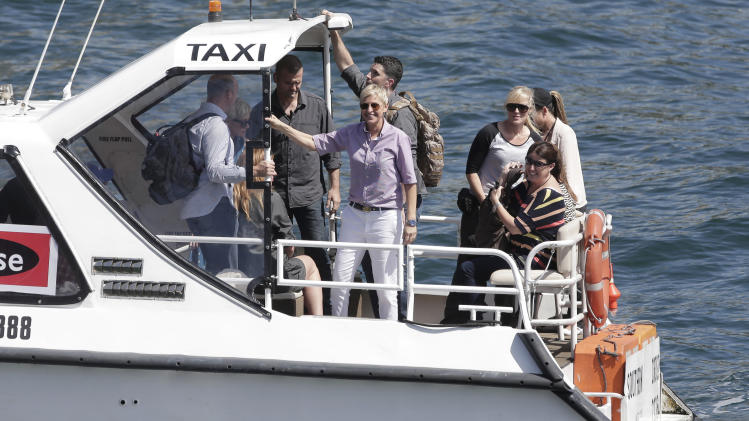 U.S. talk show host Ellen DeGeneres, center, arrives by water taxi for the recording of her show in Sydney, Australia, Saturday, March 23, 2013. (AP Photo/Rick Rycroft)