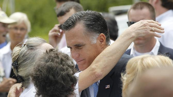 Republican presidential candidate, former Massachusetts Gov. Mitt Romney hugs supporters after he spoke about the shootings in Colorado at an event in Bow, N.H., Friday, July 20, 2012. (AP Photo/Charles Dharapak)