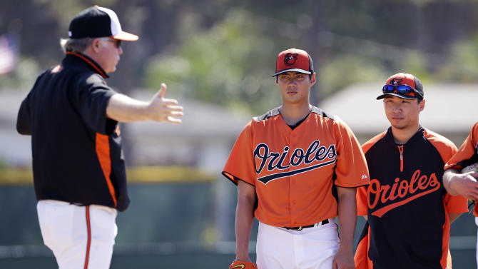 FILE - In this Feb. 13, 2013 file photo, Baltimore Orioles starting pitcher Wei-Yin Chen, center, listens to manager Buck Showalter, left, as interpreter Tim Lin, right, looks on during a baseball spring training workout  in Sarasota, Fla. A new rule in Major League Baseball that lets interpreters join managers and coaches on the mound when pitchers aren't fluent in English might still need some tweaking. The rule has already been used in spring training. (AP Photo/Charlie Neibergall, File)