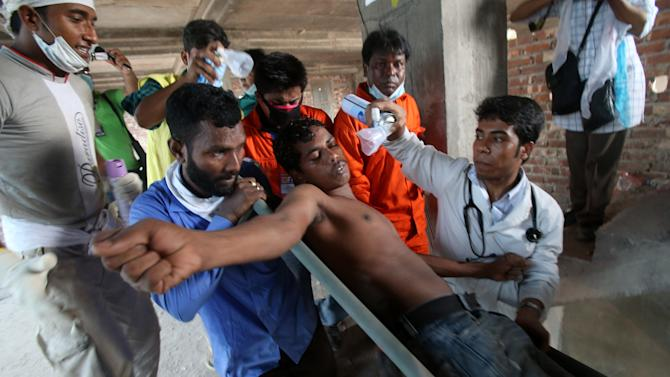 In this photo taken on Saturday April 27, 2013,  a volunteer worker is assisted to medical aid on a stretcher as he experienced a sudden loss of Oxygen when trying to help with rescue work. When the Rana Plaza, a garment factory building collapsed, many of the first responders were neighborhood residents, fellow garment workers, relatives of the missing and charity workers, and they repeatedly took some of the most dangerous work.(AP Photo/Wong Maye-E)
