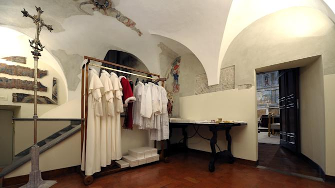 This picture made available Tuesday, March 12, 2013 by the Vatican newspaper L'Osservatore Romano shows the three sizes of the pope's garments and shoe boxes in a room next to the Sistine Chapel, seen through the door at right, at the Vatican. Cardinals enter the Sistine Chapel on Tuesday to elect the next pope amid more upheaval and uncertainty than the Catholic Church has seen in decades: There's no front-runner, no indication how long voting will last and no sense that a single man has what it takes to fix the many problems. The three identical white outfits in small, medium and large for the new pontiff's first appearance on the balcony of St. Peter's Basilica are delivered to the Vatican before the start of the conclave and left in a room next to the Sistine Chapel, where the newly elected pope changes into his new clothes. (AP Photo/L'Osservatore Romano, ho)