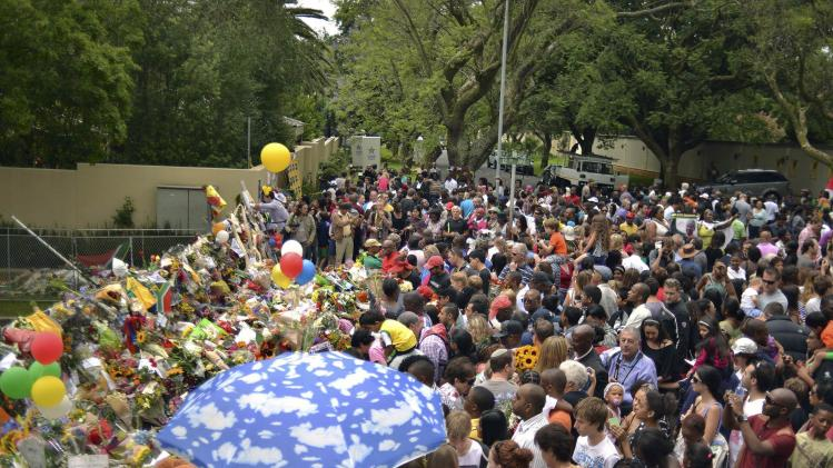 People gather to offer flowers and messages outside the Houghton home of the late former South African President Nelson Mandela in Johannesburg