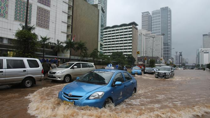 A taxi wades through a flooded street in Jakarta, Indonesia Friday, Jan. 18, 2013.  Indonesia's army deployed rubber boats in the capital's business district on Thursday to rescue people trapped in floods that inundated much of the city of 14 million people.(AP Photo/Achmad Ibrahim)