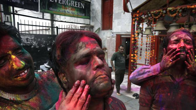 Indian men smear colors on each other's faces as they celebrate Holi in New Delhi, India , Wednesday, March 27, 2013. Holi, the festival of colors celebrates the arrival of spring among other things.(AP Photo/Manish Swarup)
