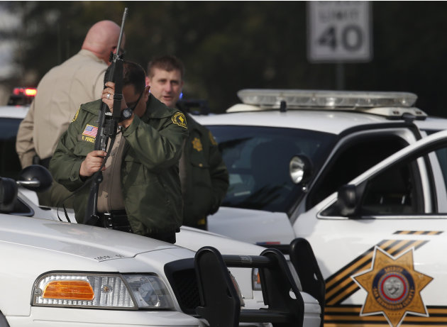 A San Bernardino County sheriff's deputy stands guard near the area where a shooting took place in Riverside, Calif, Thursday, Feb. 7, 2013. Police launched a massive manhunt for a former Los Angeles
