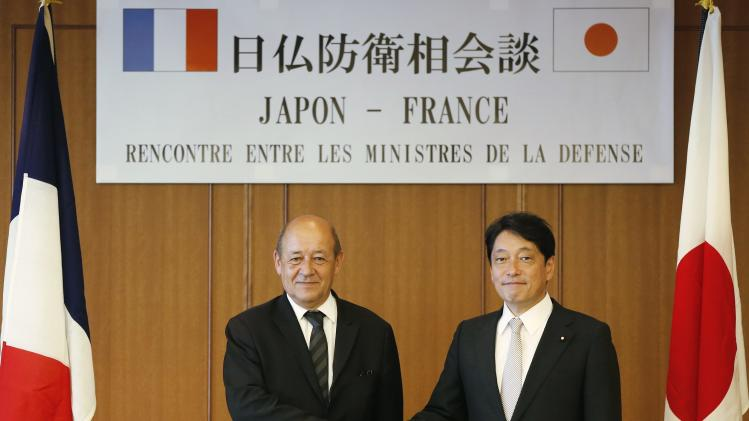Le Drian shakes hands with Onodera before their meeting at the Defense Ministry in Tokyo