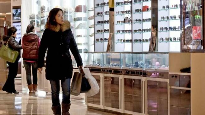 """A woman shops in a Beijing mall: """"The economy has officially exited its slowdown,"""" Chinese officials said."""