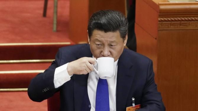 Chinese President Xi Jinping drinks from a cup during the opening of the annual full session of the National People's Congress, the country's parliament, at Great Hall of the People, in Beijing