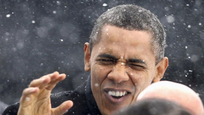 In this March 1, 2012 file photo, President Obama waves to the crowd as he walks through a snowstorm after getting off Air Force One in Manchester, N.H. (AP Photo/Winslow Townson, File)