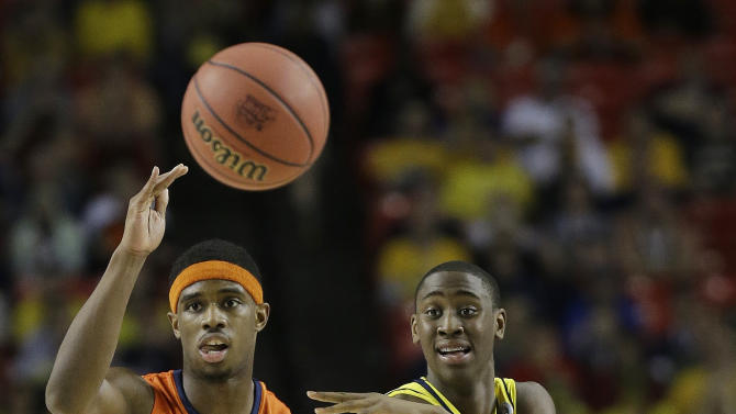 Michigan's Caris LeVert (23) passes the ball as Syracuse's C.J. Fair (5) looks on during the second half of the NCAA Final Four tournament college basketball semifinal game Saturday, April 6, 2013, in Atlanta. (AP Photo/David J. Phillip)