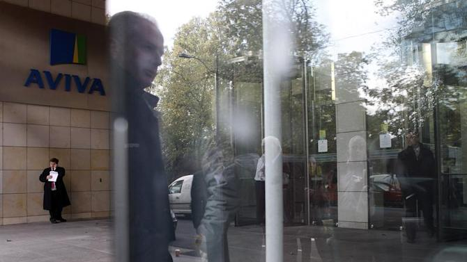 A man is reflected in a window near the entrance to the AVIVA headquarters building in Dublin.
