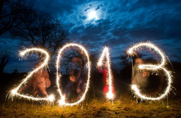 "Posed picture taken with long exposure time on December 26, 2012 shows four persons writing the date ""2013"" with sparklers in the evening sky near Sieversdorf, eastern Germany.       AFP PHOTO / PATRI"