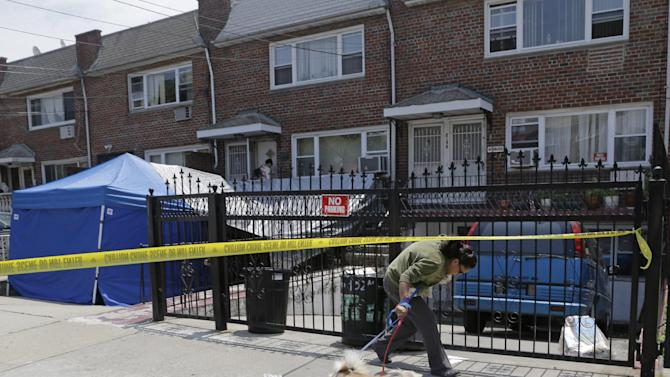 """A woman ducks under crime scene tape in front of a New York city house once occupied by a famous gangster, Tuesday, June 18, 2013, in New York. The work started Monday at the home of James Burke, a Lucchese crime family associate known as """"Jimmy the Gent."""" He was the inspiration for Robert De Niro's character in the 1990 Martin Scorsese movie """"Goodfellas."""" Burke died behind bars in 1996, two decades after authorities say he masterminded a nearly $6 million robbery at New York's Kennedy Airport, one of the largest cash thefts in American history. The Queens house is still owned by the Burke family, but others now live there. (AP Photo/Kathy Willens)"""