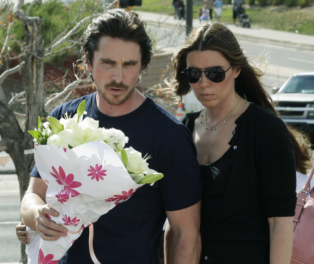 Actor Christian Bale and his wife Sibi Blazic carry flowers to place on a memorial to the victims of Friday's mass shooting, Tuesday, July 24, 2012, in Aurora, Colo. Twelve people were killed when a g