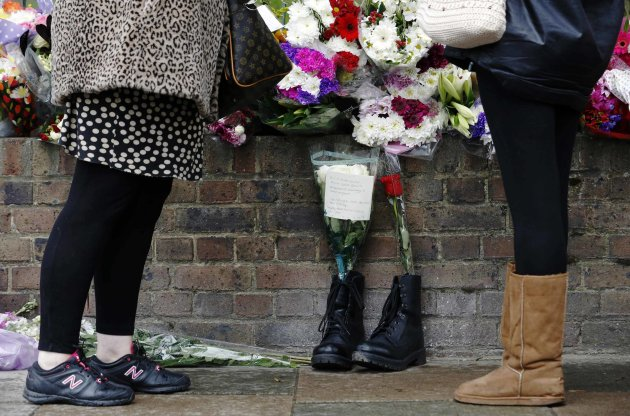 People stand near a pair of army boots and floral tributes for Drummer Lee Rigby near the scene of his killing in Woolwich