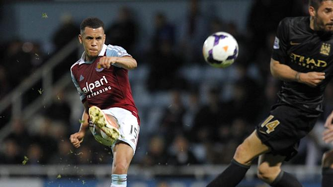 West Ham United's English midfielder Ravel Morrison (L) has a shot at goal during an English Premier League football match between West Ham United and Manchester City at Upton Park in London, on October 19, 2013