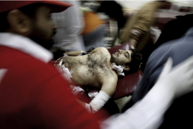 A Pakistani man who was injured in a suicide bombing is rushed by volunteers to a hospital in Peshawar, Pakistan, Friday, Feb. 1, 2013. A suicide bomber detonated his explosives outside a Shiite mosqu