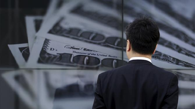 File photo of a businessman looking at a screen displaying a photo of U.S. $100 banknotes in Tokyo
