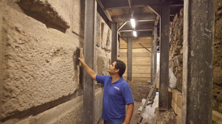In this picture taken Tuesday, Aug. 2, 2011, Eli Shukron, an Israel Antiquities Authority archaeologist cleans stones making part of an underground section of the Western Wall at the end of what archaeologists say is a 2,000-year-old drainage tunnel leading to Jerusalem's Old City. The excavation of an ancient drainage tunnel beneath Jerusalem has yielded new artifacts from a war here 2,000-years ago, archaeologists said Monday, Aug. 8, 2011, shedding light on a key episode of the past buried under today's politically combustible city. (AP Photo/Dan Balilty)