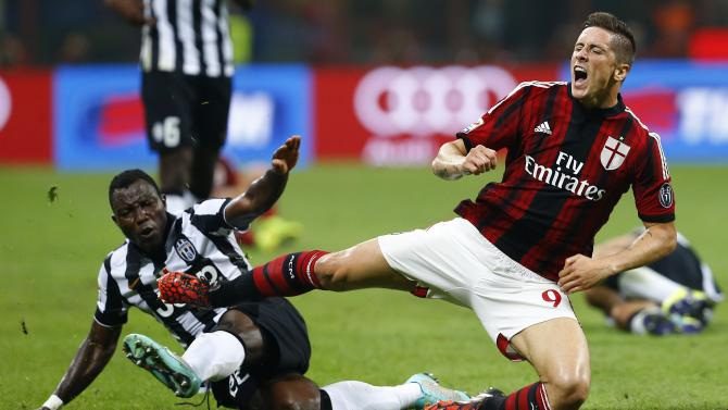 AC Milan's Torres is tackled by Juventus' Asamoah during their Italian Serie A soccer match at the San Siro stadium in Milan