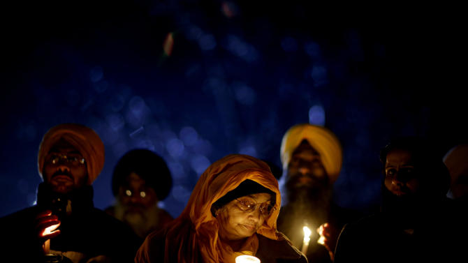 Surjit Kaur Gill, of Worcester, Mass., joins a group of Sikhs from around the Northeastern U.S., in a moment of prayer as a memorial service is broadcast over a loudspeaker outside Newtown High School for the victims of the Sandy Hook Elementary School shooting, Sunday, Dec. 16, 2012, in Newtown, Conn. (AP Photo/David Goldman)