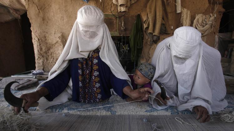 Ethnic Hazara Afghan women weave a carpet at a makeshift workshop at their house in Khorasan Refugee Camp, on the outskirts of Peshawar