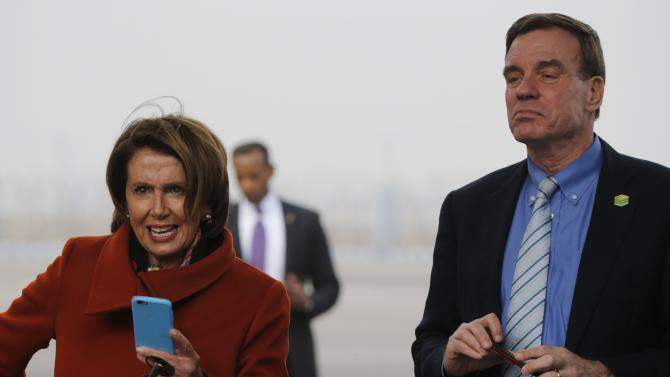 U.S. House Minority Leader Pelosi and U.S. Senator Warner wait to take pictures with phones of U.S. President Obama as he disembarks from Air Force One at Air Force Station Palam in New Delhi